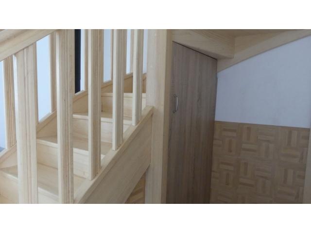 Un placard de rangement en dessous de l'escalier en bois qui permet de ne gâcher aucun espace
