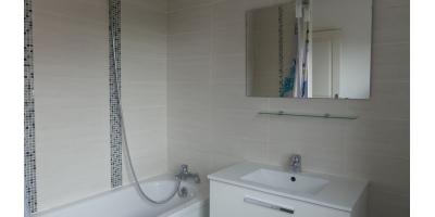 La salle de bain est entièrement carrelée avec soin